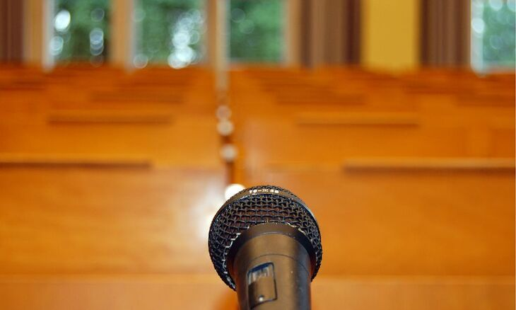 Microphone stands before empty rows in a lecture hall