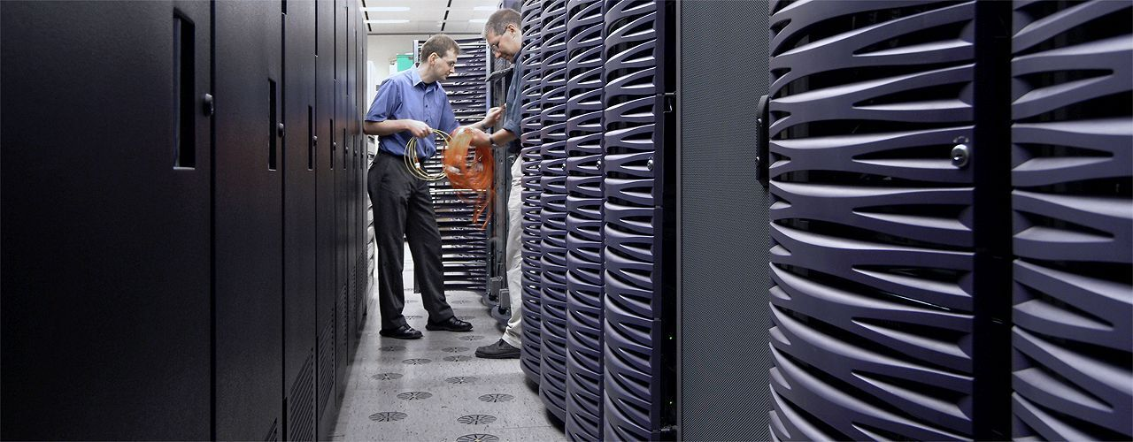 Two men working at a supercomputer