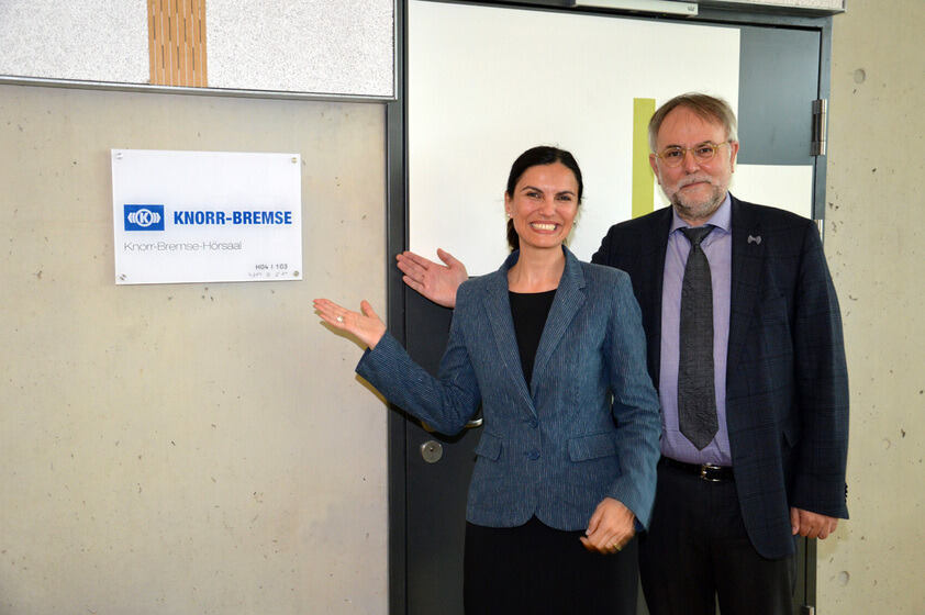 Two individuals next to a sign for the Knorr-Bremse lecture hall